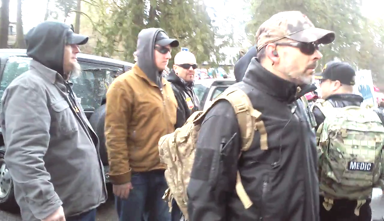 III% Militia members are seen protecting KKK Imperial Wizard and National Socialist Movement member Steven Shane Howard at a far right Trump Rally on 3/4/2017